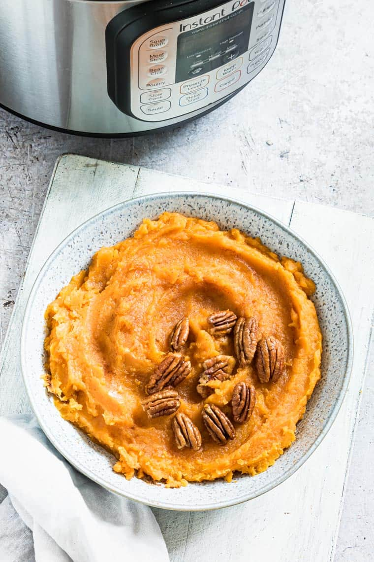 mashed sweet potatoes in a serving dish next to the Instant Pot