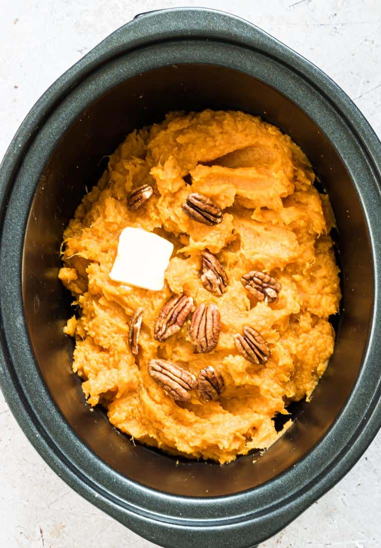 slow cooker mashed sweet potatoes in the slow cooker and topped with butter and toasted nuts
