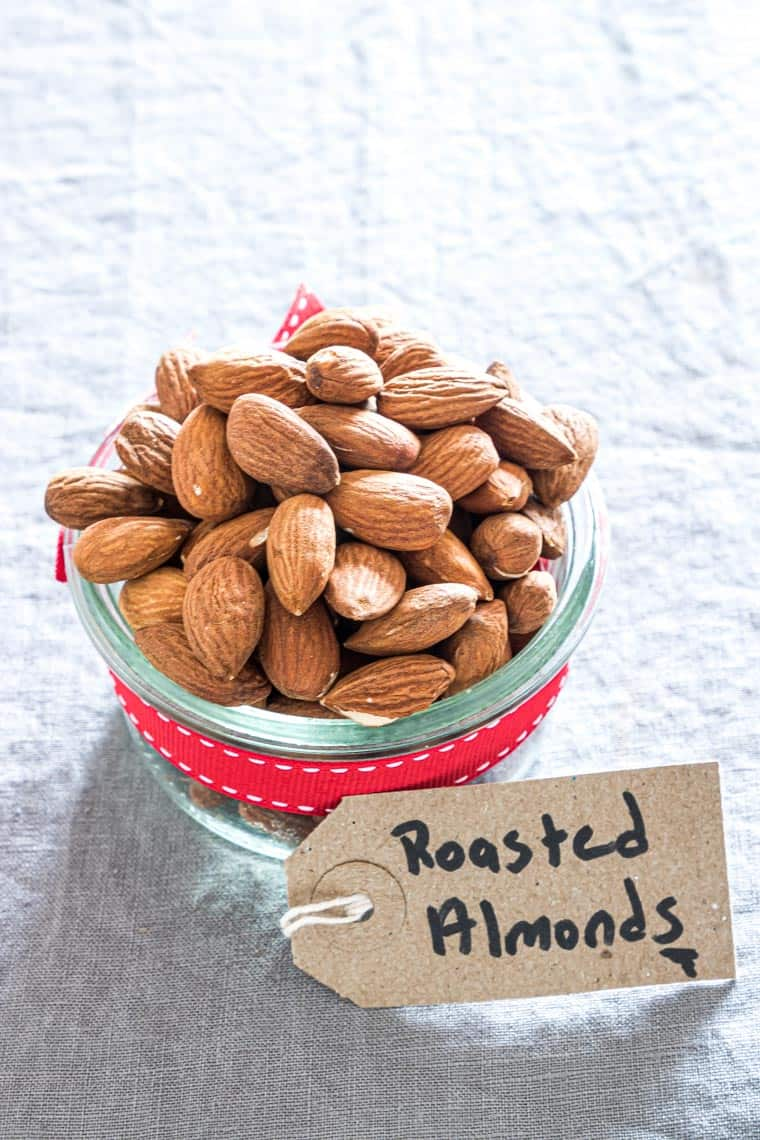 air fryer roasted almonds in a glass jar that is wrapped with a ribbon and gift tag