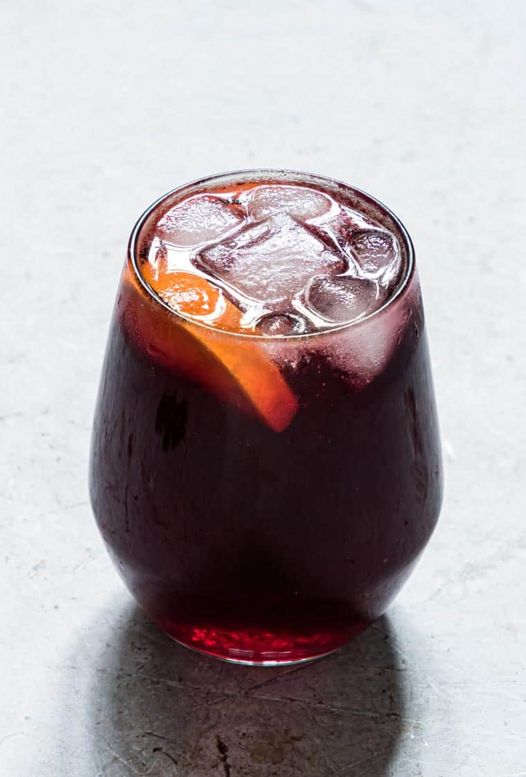 Jamaican Sorrel Drink served in a glass with ice cubes and orange wedges