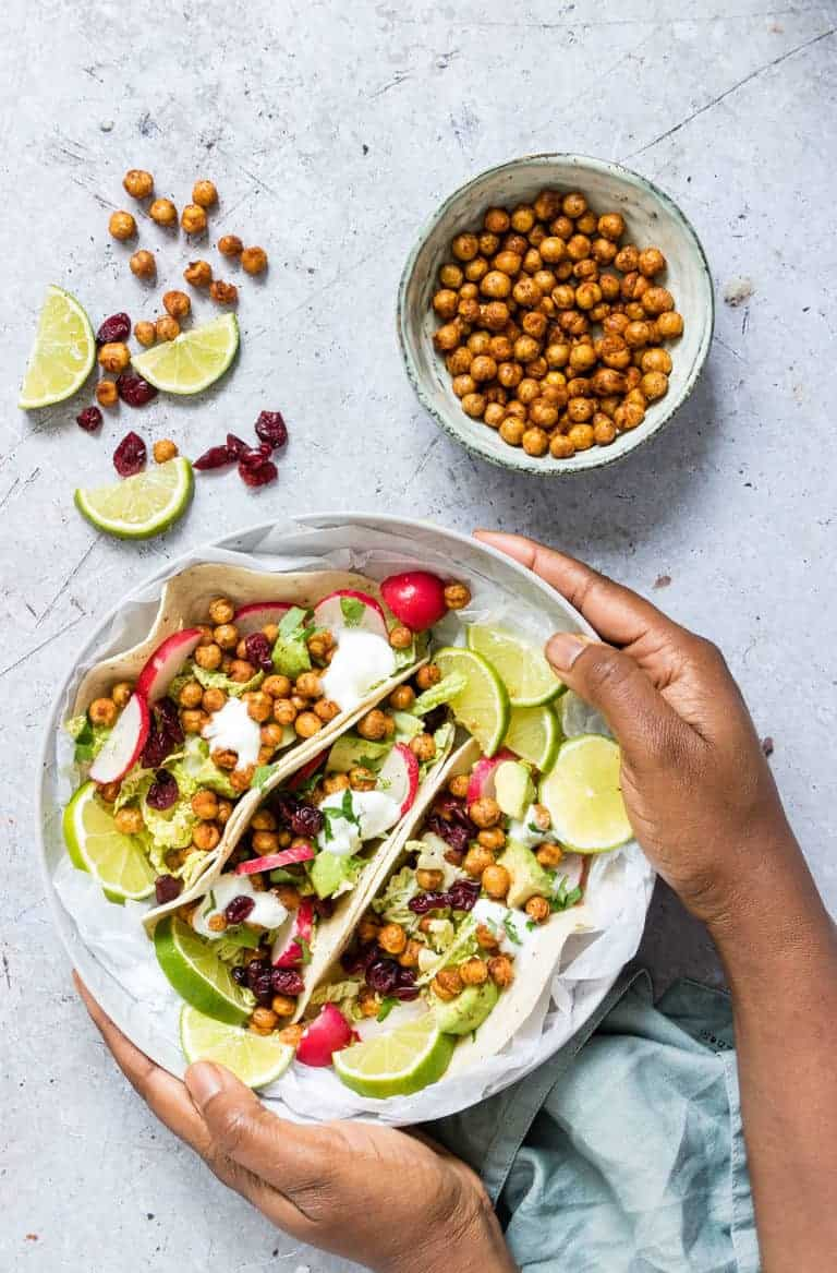 air fryer chickpea tacos in a bowl being held by some hands with chickpeas and limes