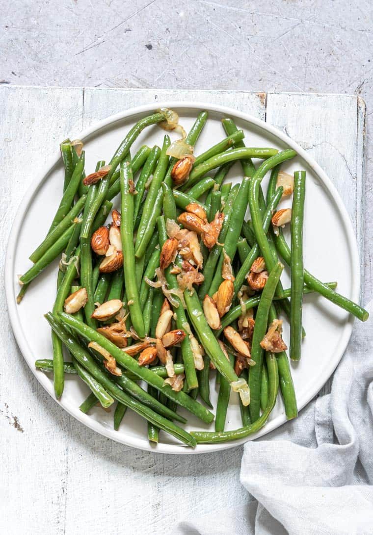 close up view of the completed green beans almondine recipe served on a white plate with a cloth napkin