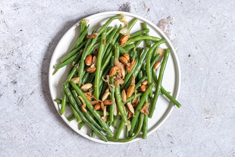 top down view of green beans almondine served on a white plate
