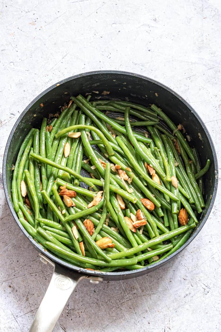 the completed green beans almondine recipe inside a skillet