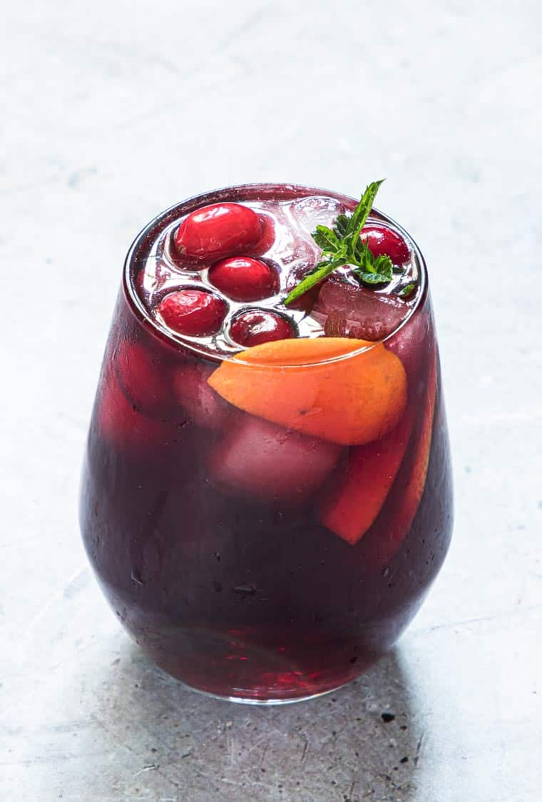 glass filled with hibiscus punch garnished with cranberries, orange and mint.