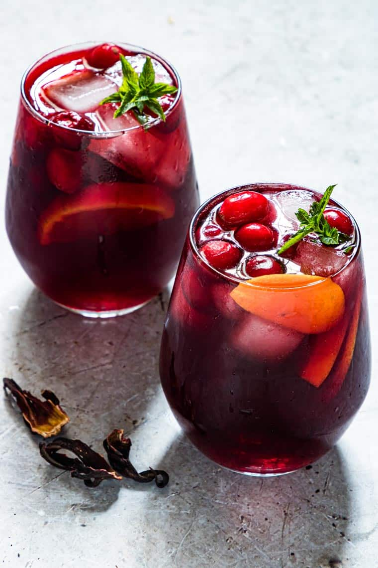 two glasses of sorrel punch set next to pieces of dried hibiscus
