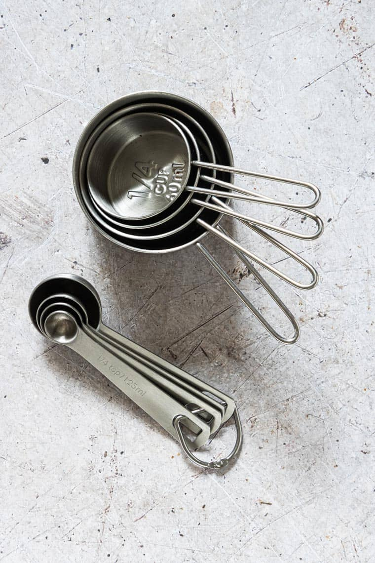 stainless steel measuring cups and spoons set on a countertop to be used to determine how many tablespoons in a cup