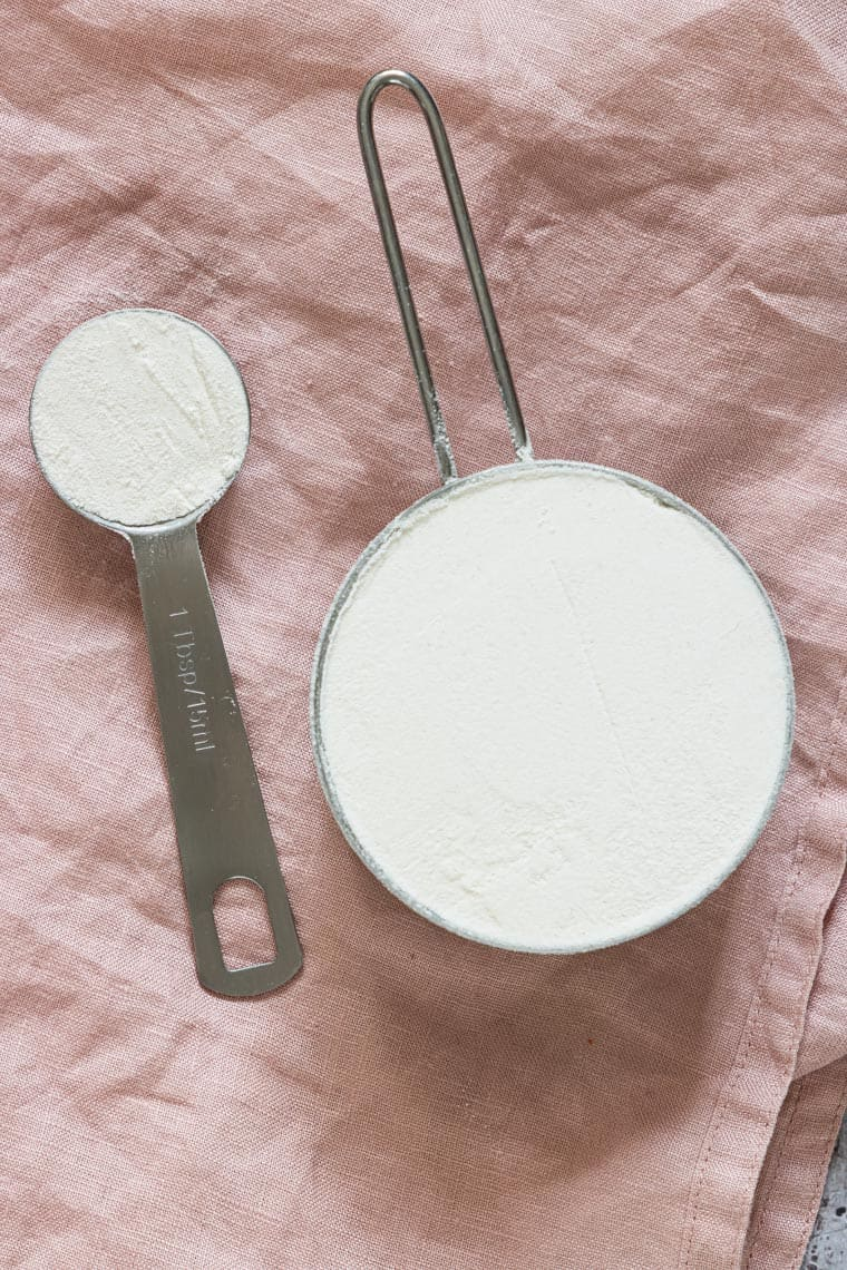 a cup of flour and a  tablespoon of flour set on top of a red linen napkin