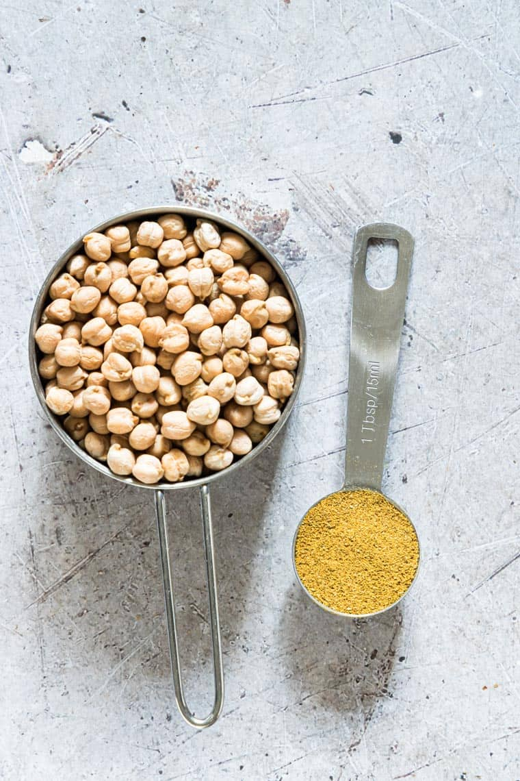 one measure cup filled with chickpeas and a tablespoons filled with curry powder