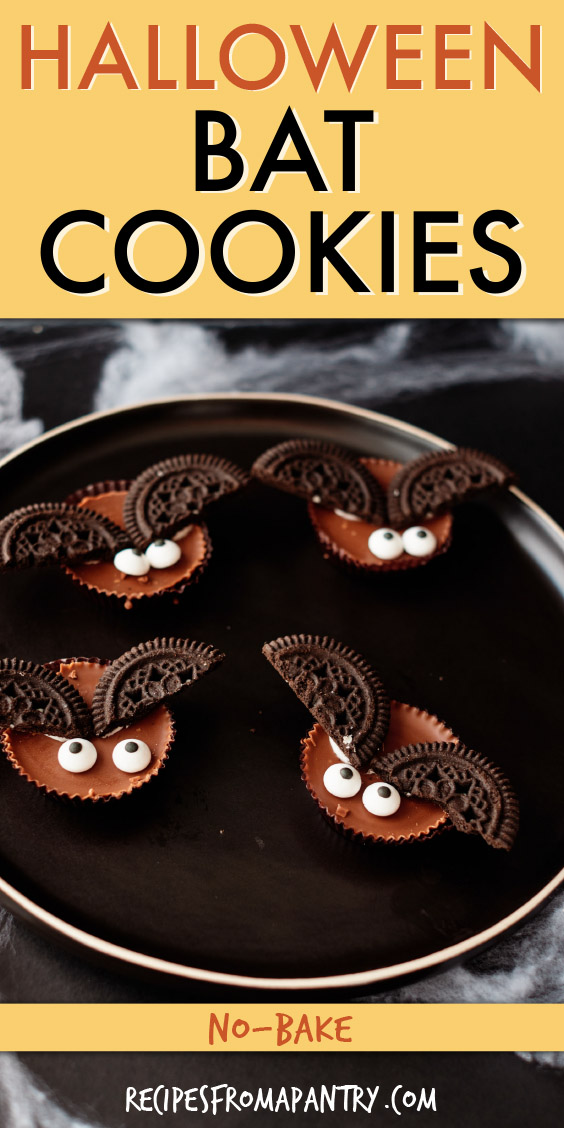four bat cookies sitting on a black plate