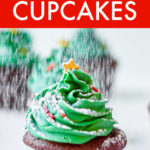 A christmas tree cupcake being sprinkled with powdered sugar