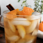 a glass of iced old fashioned cocktail garnished with orange peel