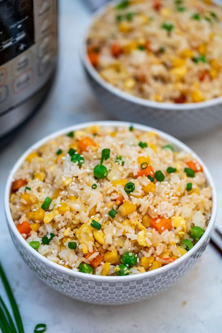 Two bowls of Instant Pot Fried Rice set next to the Instant Pot