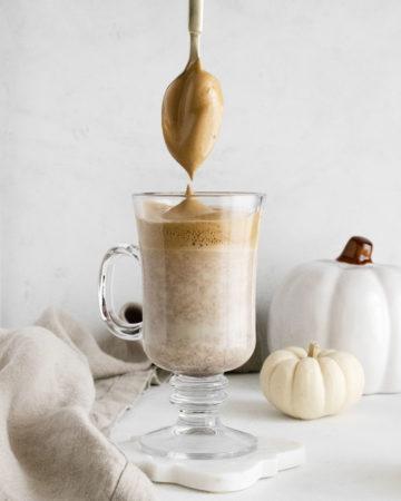 a glass of Pumpkin Spiced Whipped Coffee – Dalgona Coffee with a teaspoon