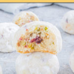 a stack of two snowball cookies with a bite taken out of the top one.