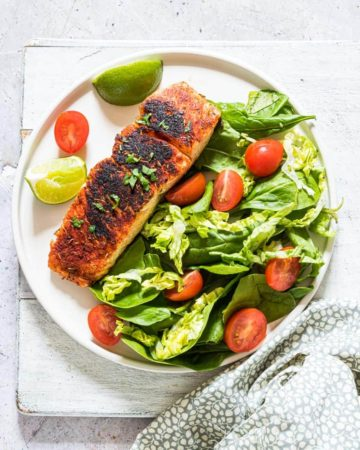 easy blackened salmon served on a plate of salad