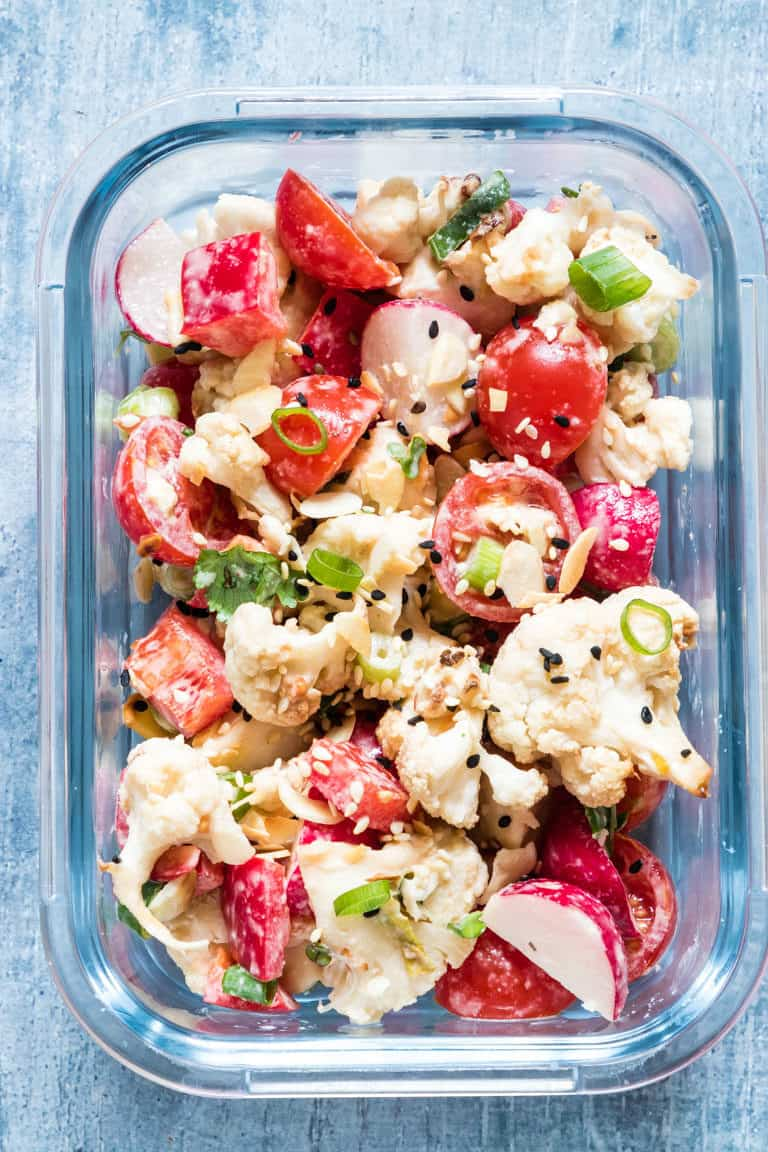 close up view of one glass meal prep storage container filled with cauliflower salad recipe