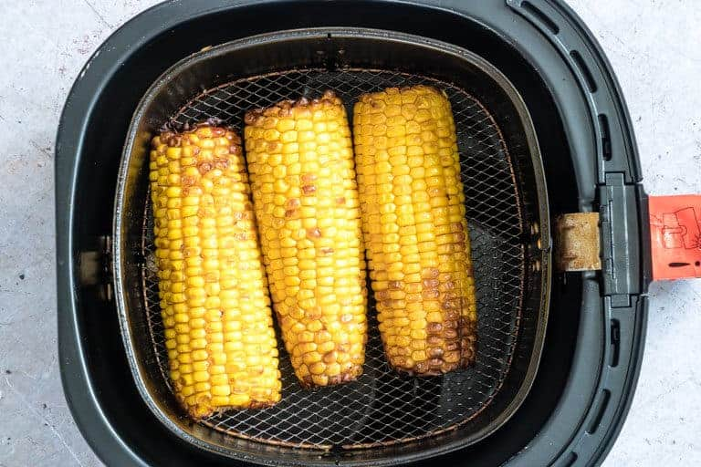 three pieces of Air Fryer Corn on the Cob inside the air fryer basket