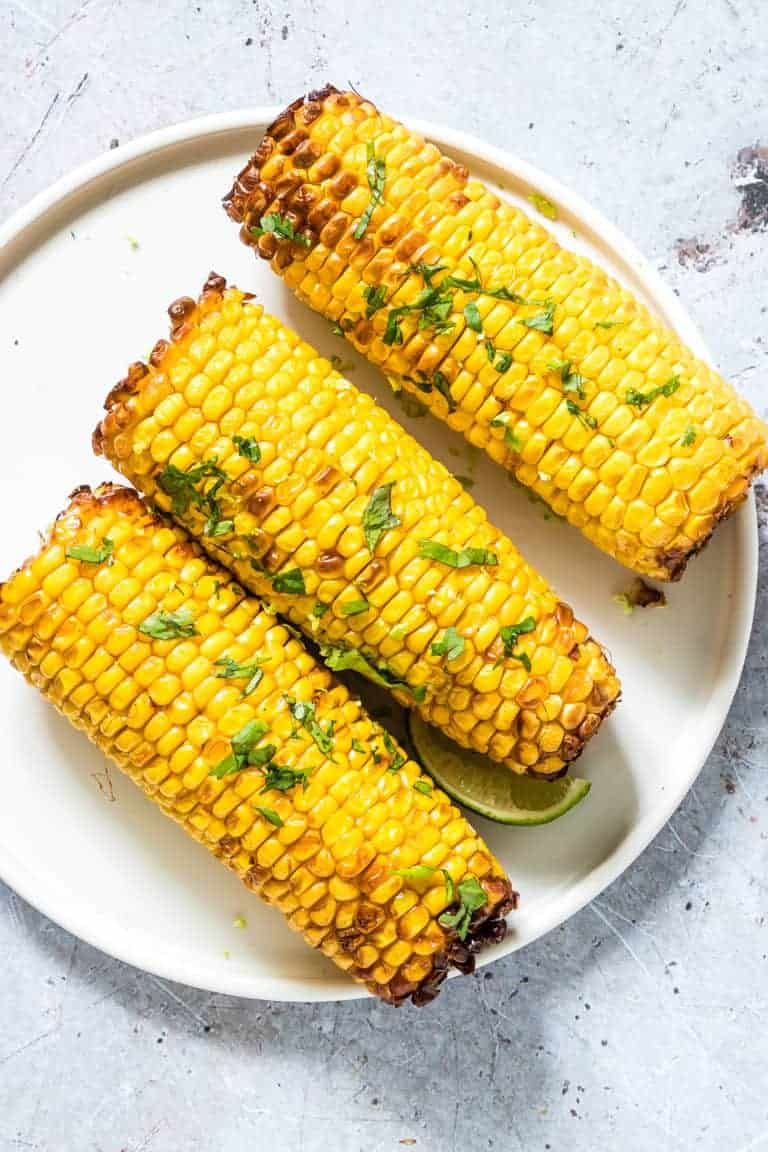 three pieces of Air Fryer Corn on the Cob served on a white plate