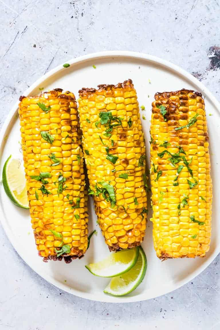 three pieces of Air Fryer Corn on the Cob topped with fresh herbs and served on a white plate with lime wedges