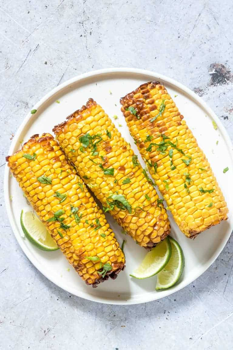 three pieces of Air Fryer Corn on the Cob topped with chopped herbs and served with lime wedges