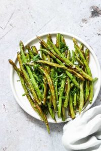 Cooked Air Fryer Green Beans served on a white dinner plate with a cloth white napkin