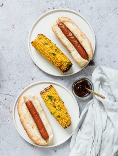 two white plates containing Air Fryer Hot Dog and Air Fryer Corn on the Cob, served with a small condiment dish and a cloth napkin