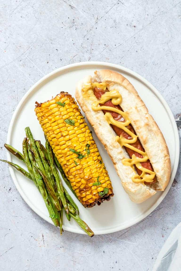 one air fryer hot dog served with an ear of air fryer corn on the cob and a portion of air fryer green beans