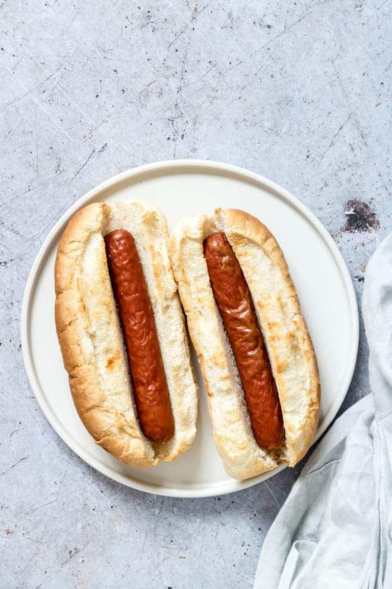 Two Air Fryer Hot Dogs on a white dinner plate and ready to be served
