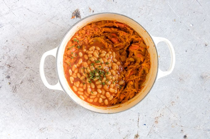 overhead shot of white pot with chakalaka with baked beans and fresh thyme on top
