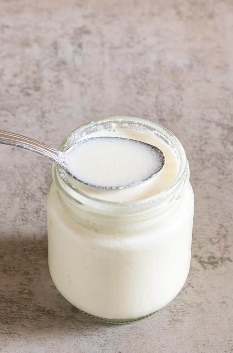 a jar of homemade buttermilk with a spoon