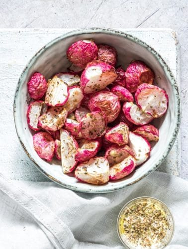 air fryer fried radishes in a bowl and served with a cup of dipping sauce