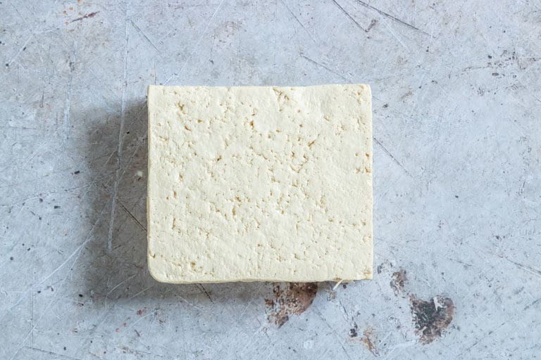 a block of extra firm tofu on a countertop ready to be used for making Air Fryer Tofu