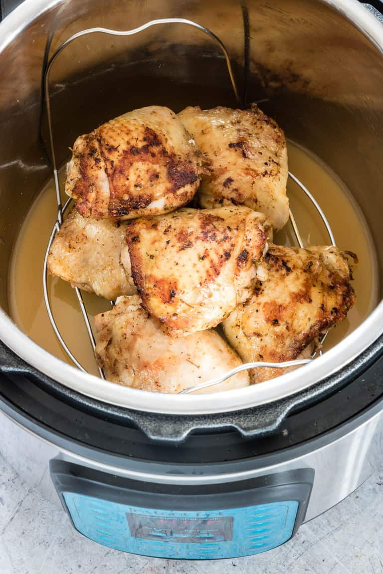 instant pot containing cooked instant pot chicken thighs in liquid with lid open