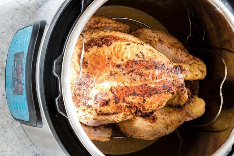 instant pot whole chicken fully cooked sitting on a trivet in instant pot