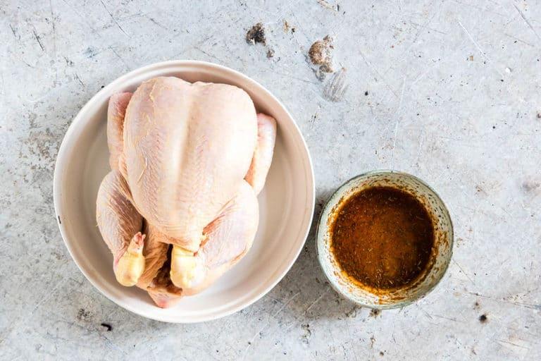 crockpot whole chicken being seasoned