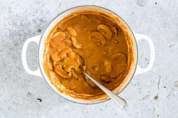 overhead shot of final mushroom masala with spoon sitting in pot
