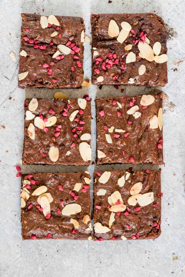 Over headshot of 6 avocado brownies (vegan brownies) that are sprinkled with dried raspberries and almonds on a grey background.