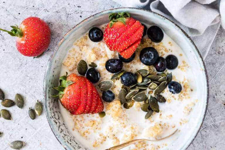 bowl of quinoa porridge with quinoa mixed with milk, strawberries, blueberries, and pumpkin seeds