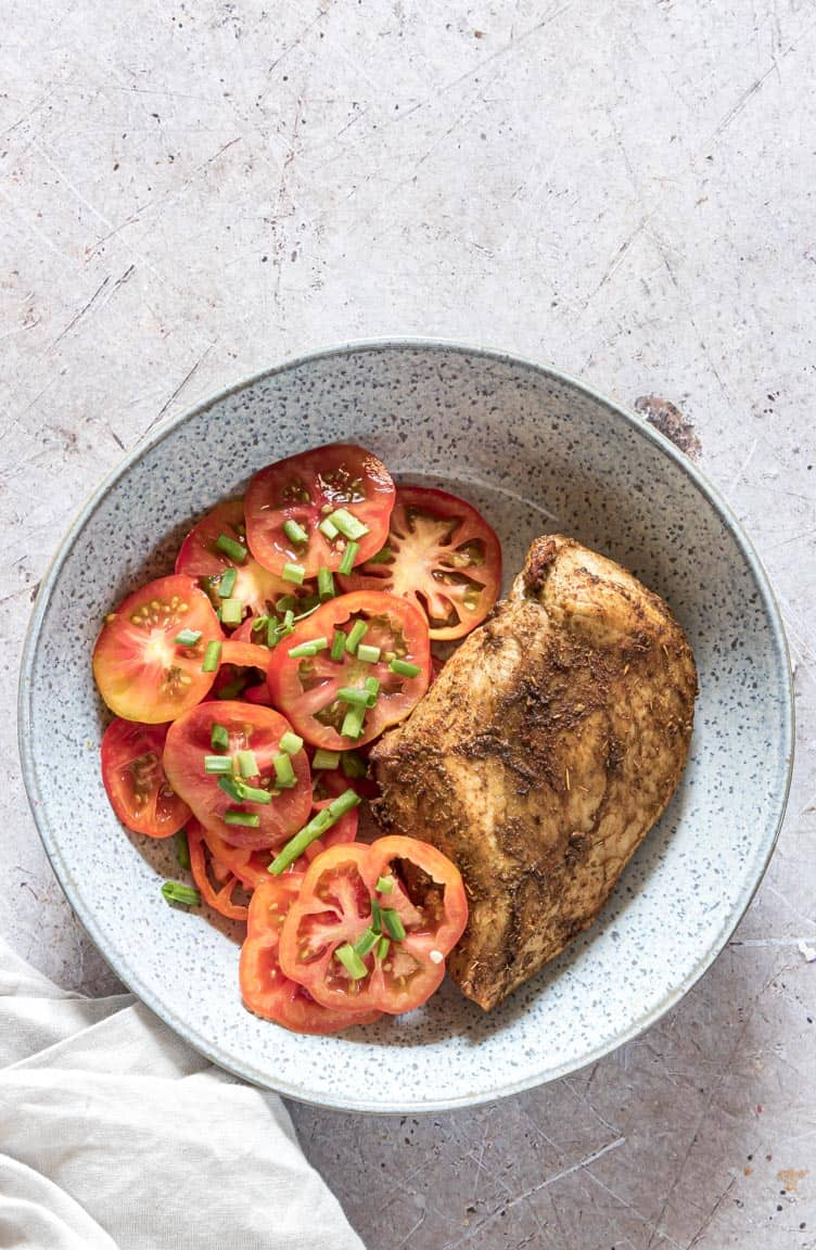 smoked chicken breast in a plate with tomato salad