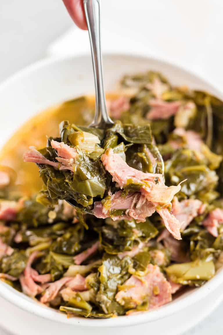 a spoon taking a serving of instant pot collard greens out of a bowl