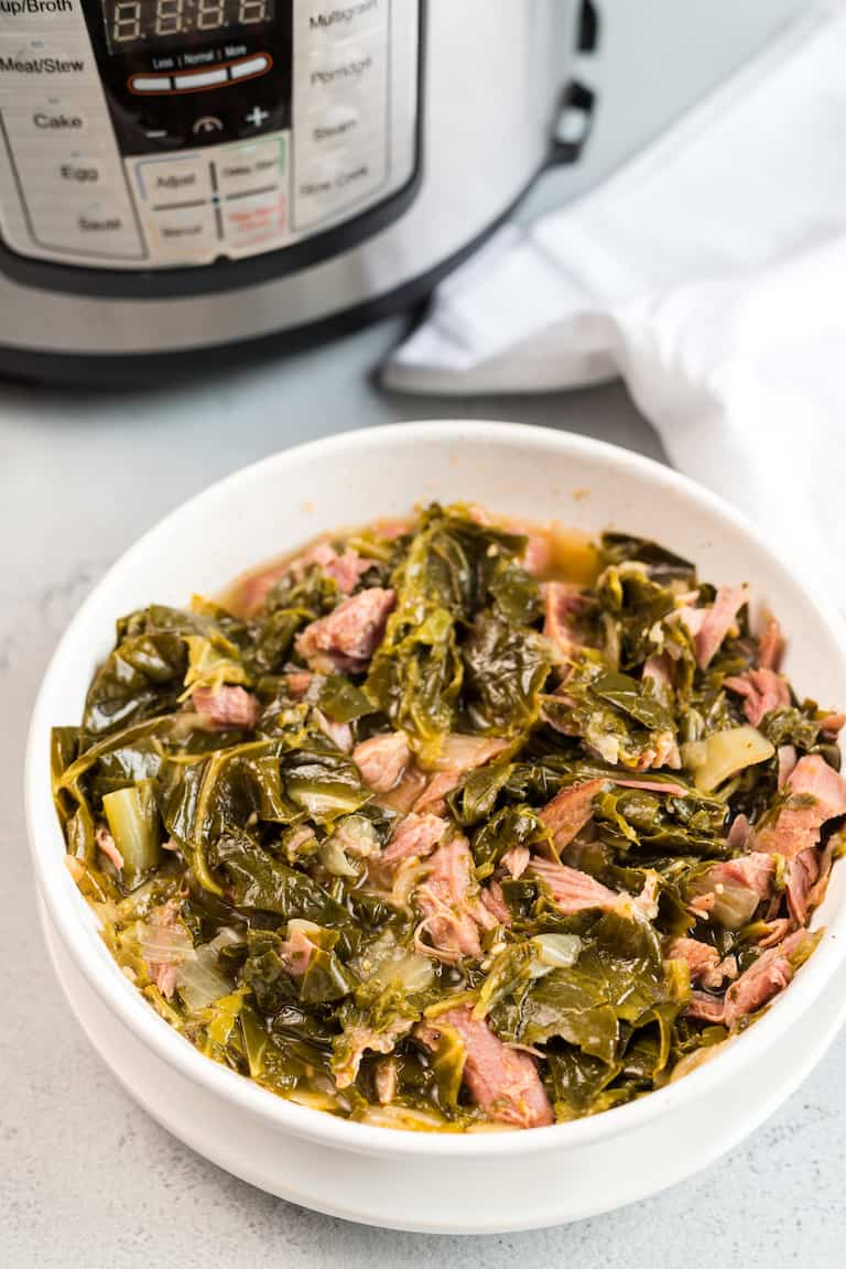 a bowl of instant pot collard greens set in front of the instant pot