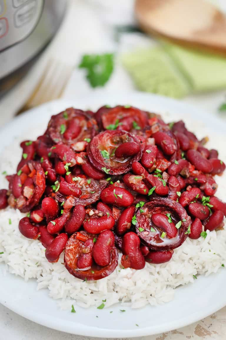 Instant Por Red Beans and Rice served on a white plate and set next to an Instant Pot