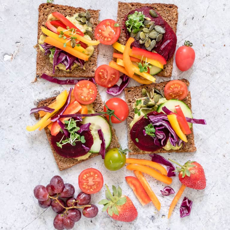a rainbow sandwich open faced next to another with fresh cut vegetables on top