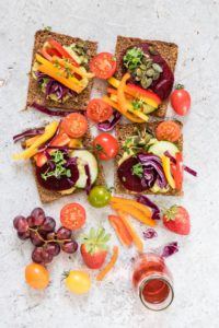 open-faced rainbow sandwich with colourful vegetables on top and around rainbow sandwiches
