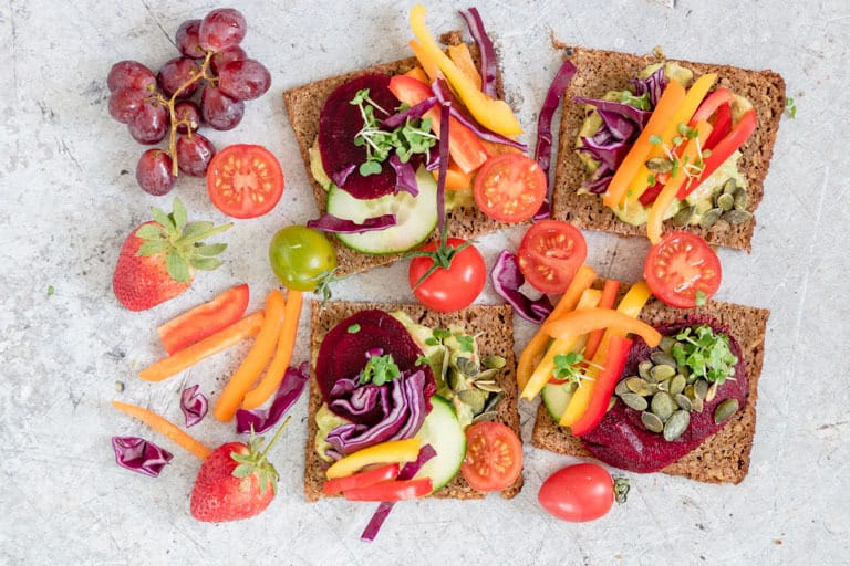 open faced rainbow sandwich next to other rainbow sandwiches, fruits and vegetables