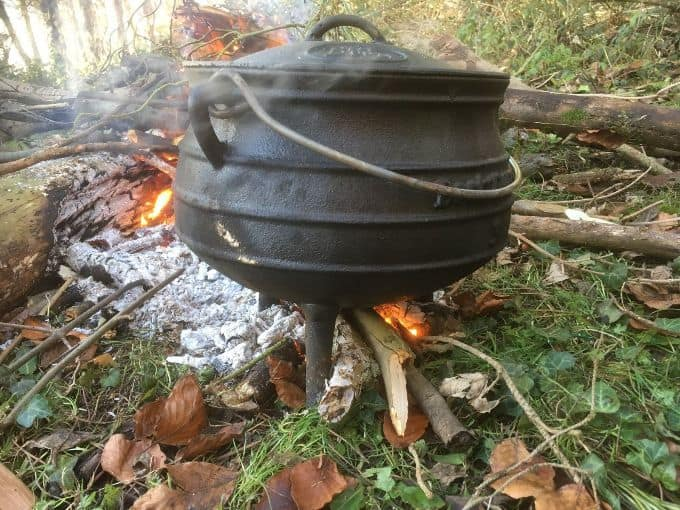 closeup of campfire stew being made in cast iron pot on leaves and brush