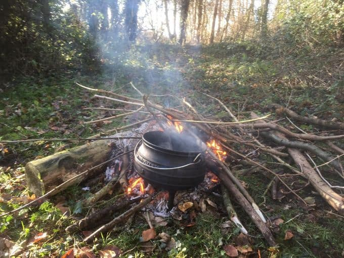 view of campfire stew on camp fire in wooded area