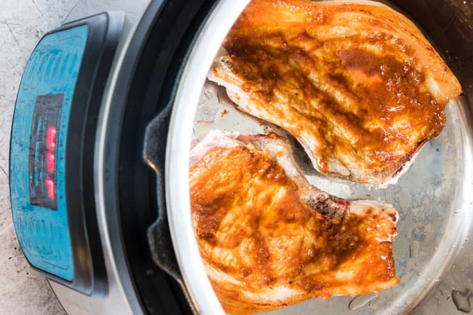 view inside instant pot with cooked instant pot pork chops with harissa paste on top