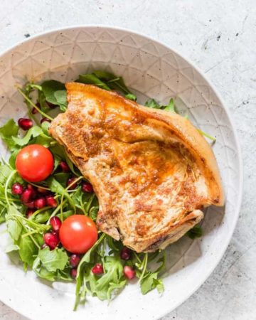 overhead view of instant pot pork chops in a white salad bowl next to salad greens